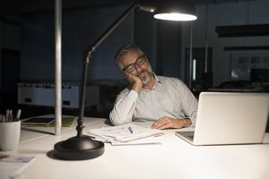 Exhausted businessman in office with laptop in the dark - RBF05279