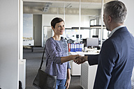 Businessman and businesswoman shaking hands in office - RBF05282