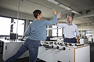 Two colleagues playing foosball and high fiving in office - RBF05285