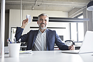 Happy businessman throwing paper plane in office - RBF05303