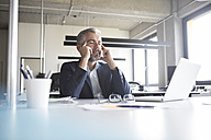 Businessman at desk in office with closed eyes - RBF05306