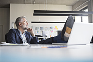 Relaxed businessman at office desk - RBF05309