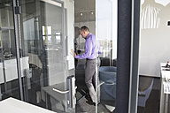 Businessman in office leaning against glass wall - RBF05339
