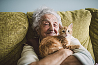 Portrait of happy senior woman cuddling with her cat on the couch - RAEF01594