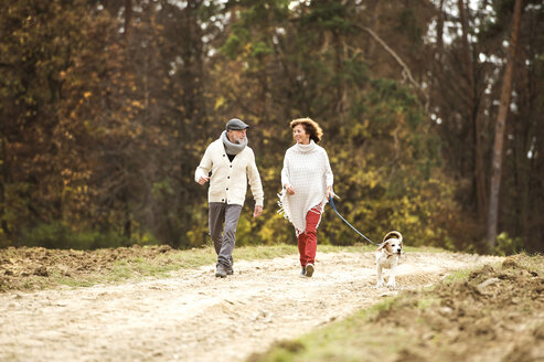 Senior couple walking in the woods with her dog - HAPF01152