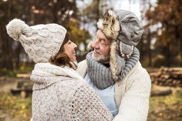 Happy senior couple looking each other in autumnal nature - HAPF01170