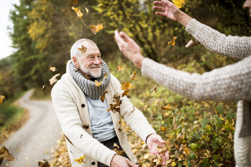 Happy senior man and his wife playing with autumn leaves - HAPF01176