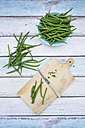 Bowl of green beans, wooden board and kitchen knife on wood - LVF05645