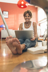 Smiling woman at home sitting on floor using laptop - MGOF02669