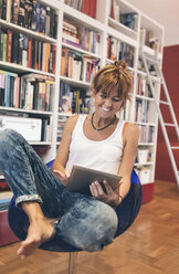 Smiling woman at home using tablet - MGOF02675