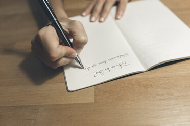 Woman writing in notebook with a classic fountain pen - MGOF02684