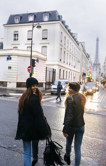 France, Paris, two young women walking on the street with the Eiffel Tower in the background - MGOF02686