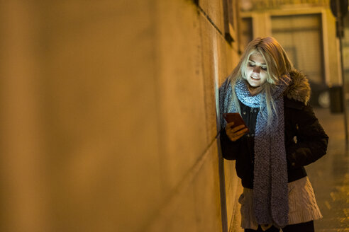 Young woman leaning against facade at night looking at her smartphone - SIPF01146