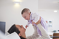 Mother holding up baby girl at home - SIPF01152