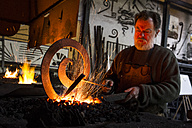 Blacksmith at work in his workshop - ABZF01581