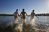 Back view of friends running in a lake - FMKF03279