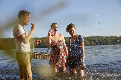 Playful friends splashing in a lake taking a drink - FMKF03282