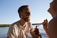 Happy couple at a lake taking a healthy snack - FMKF03285