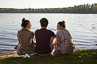 Friends sitting at a lake - FMKF03291