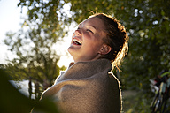 Laughing young woman wrapped in a blanket at sunset - FMKF03294