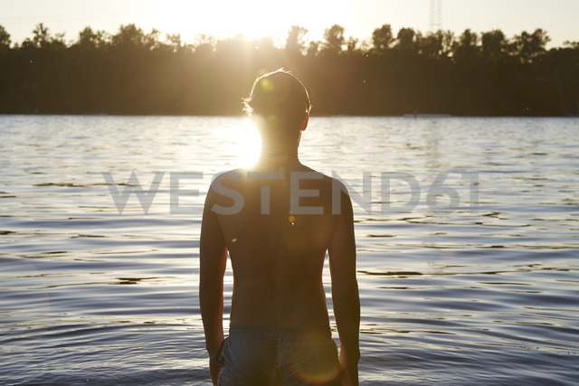 Back view of man in a lake at sunset - FMKF03300 - Jo Kirchherr/Westend61