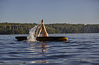 Two women jumping into water from paddleboard - FMKF03303