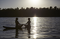 Two women doing yoga on paddleboard at sunset - FMKF03306