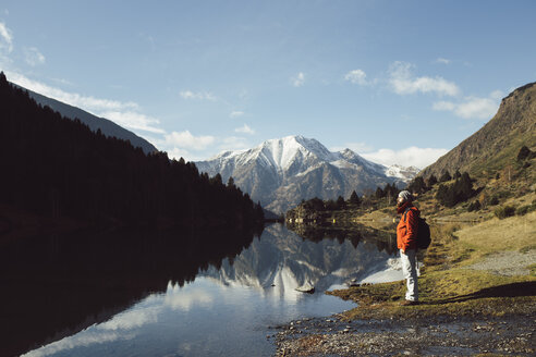 France, Pyrenees, Pic Carlit, hiker taking a rest at mountain lake - KKAF00163