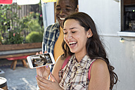 Happy young woman with boyfriend showing cell phone picture - WEST22141