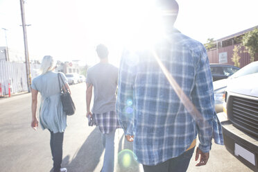 Three young people walking on the street in sunshine - WEST22153