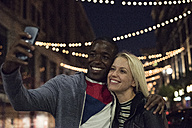 Happy young man with girlfriend taking a selfie at night - WEST22156
