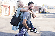 Happy young man carrying girlfriend piggyback - WEST22162