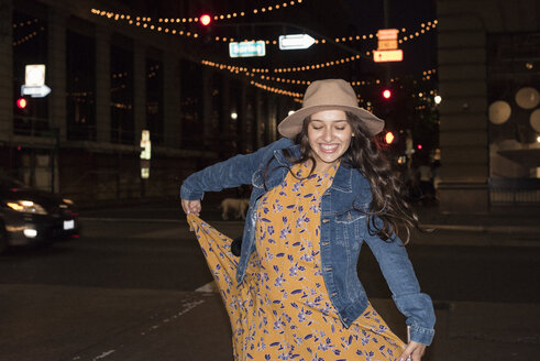 Happy young woman on the street at night - WEST22198