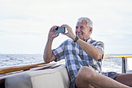 Senior man on a boat trip taking a picture - WESTF22225