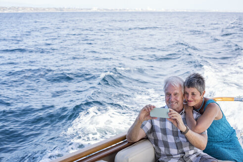 Smiling couple on a boat trip taking a selfie - WESTF22237