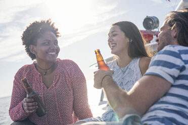 Happy friends on a boat trip having a beer - WESTF22243