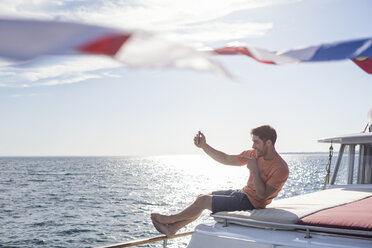 Young man on a boat posing for a selfie - WESTF22264