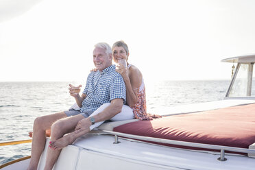 Happy couple having a drink on a boat trip - WESTF22285