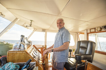 Confident senior man steering a boat - WESTF22291