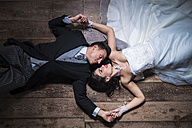 Bridal couple lying on wooden floor - SIPF01157