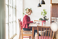 Young woman using laptop in a cafe - UUF09431