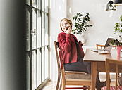 Smiling young woman using cell phone in a cafe - UUF09434