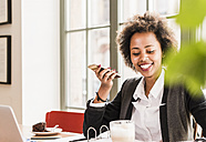 Smiling young woman using cell phone in a cafe - UUF09449