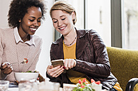Two young women with cell phone meeting in a cafe - UUF09461