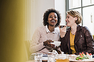 Two happy young women using cell phone in a cafe - UUF09464