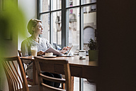 Young woman with tablet in a cafe looking out of window - UUF09479