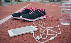 Sport shoes, smartphone with earbuds and bottle of water on tartan track - DAPF00511