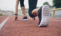 Woman on tartan track in starting position - DAPF00520