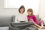 Girl sitting on the couch using mini tablet while her sister watching her - LVF05673