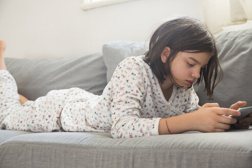 Girl lying on the couch using mini tablet - LVF05676